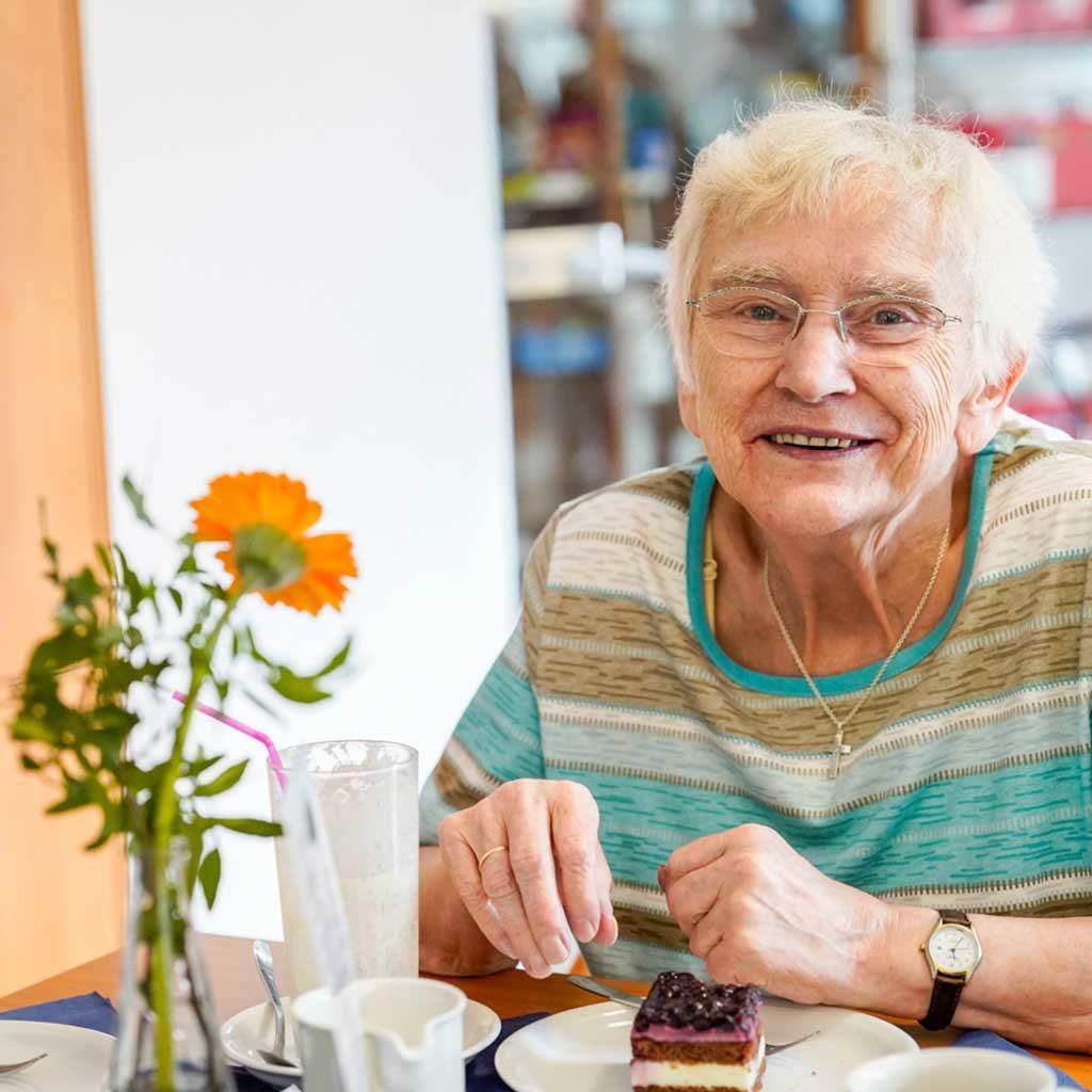 Eine Bewohnerin lächelt während sie ein Stück Kuchen isst