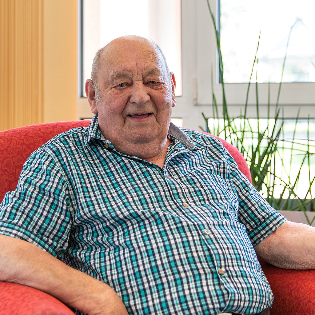 Bewohner Bernhard sitzt in einem Sessel