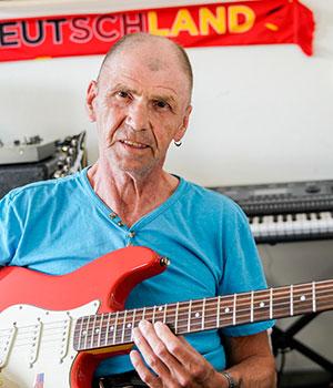 Bewohner Horst-Jürgen beim Gitarre spielen in seinem Zimmer