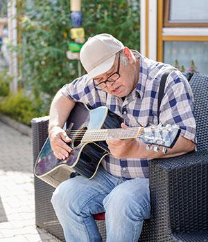 Bewohner Reinhard sitzt draußen in einem Sessel während er seine Gitarre stimmt
