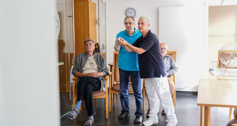 Bewohner spielen an Bowling an einer Spielekonsole während eine Pflegekraft hilft
