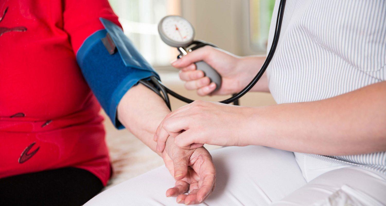 Eine Pflegekraft prüft den Blutdurck einer Bewohnerin