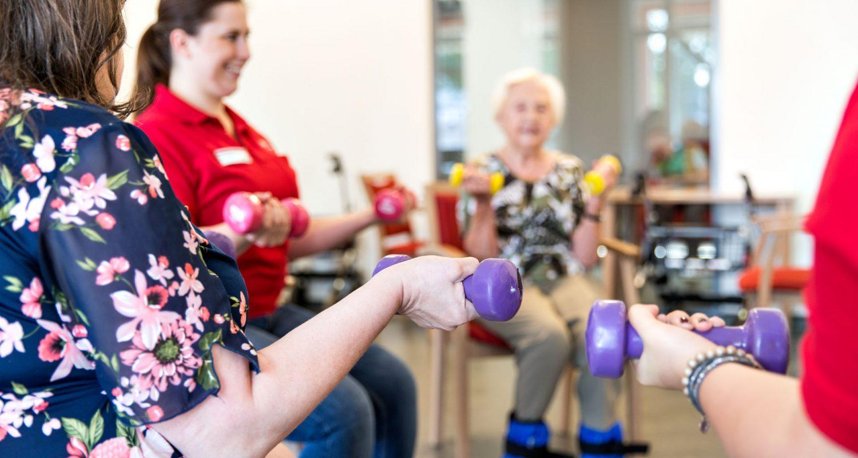 Bewohnerinnen und Pflegerin bei einer gemeinsamen sportlichen Aktivität