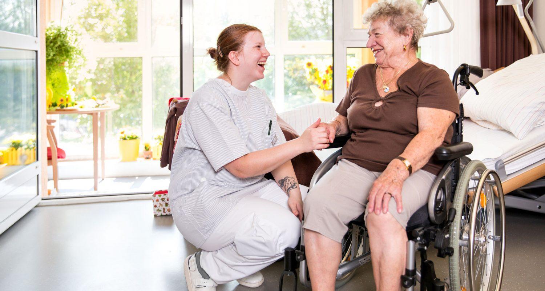 Bewohnerin und Pflegerin beim fröhlichen Gespräch miteinander