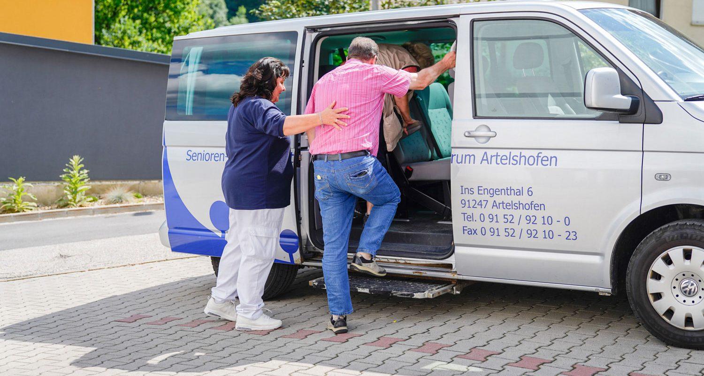 Eine Pflegekraft hilft einem Bewohner in den internen Bus