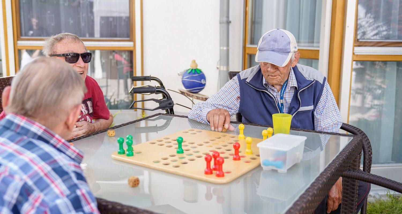 Drei Bewohner spielen draußen ein Brettspiel